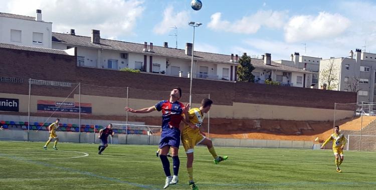 Un jugador del Mercantil i un altre del Badalona lluiten per una pilota dividida | Núria García
