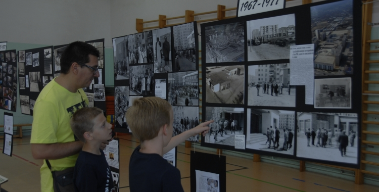 Un pare i dos nens miren les fotografies dels primers anys de l'escola. Foto: Ràdio Sabadell