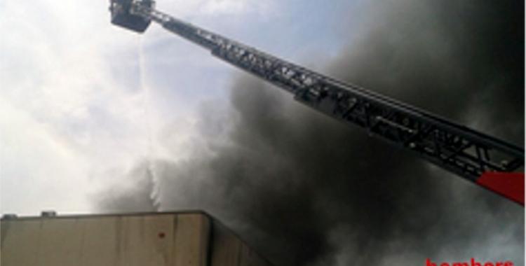 Els Bombers treballen amb una grua per extingir les flames