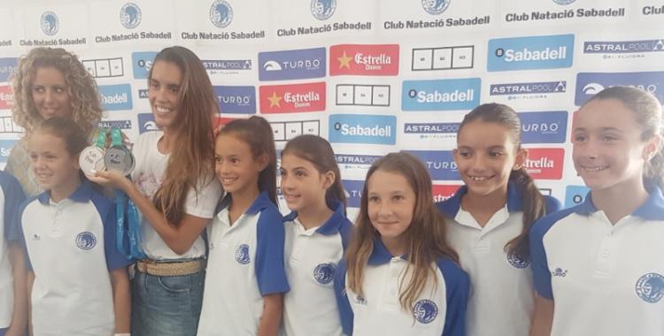 Ona Carbonell envoltada de nenes del seu campus i amb les dues medalles assolides a Hongria