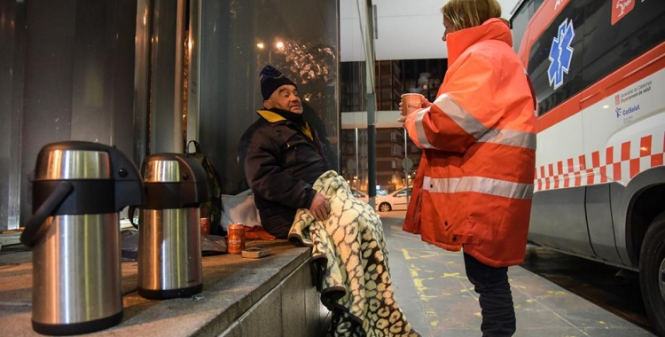 Un tècnic de Creu Roja atenent una persona que dorm al carrer | Roger Benet