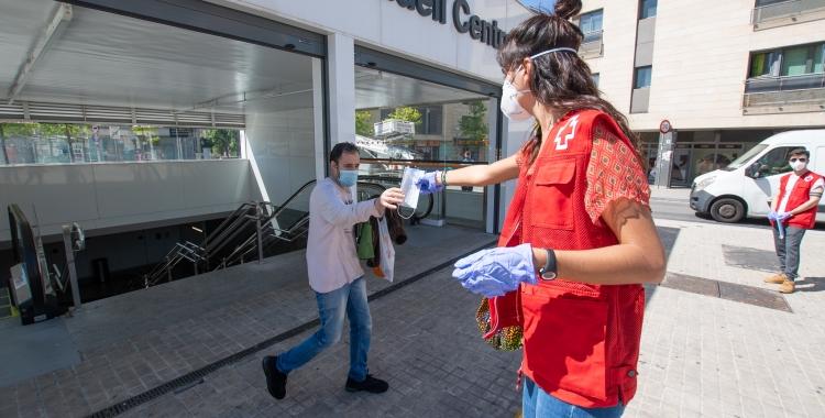 Voluntaris de Creu Roja repartint mascaretes a la sortida dels Ferrocarrils   Roger Benet