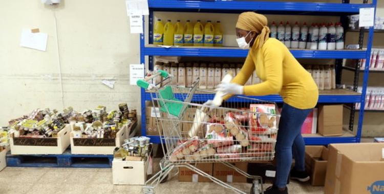 Imatge d'una voluntària de Càritas omplint un carretó | ACN