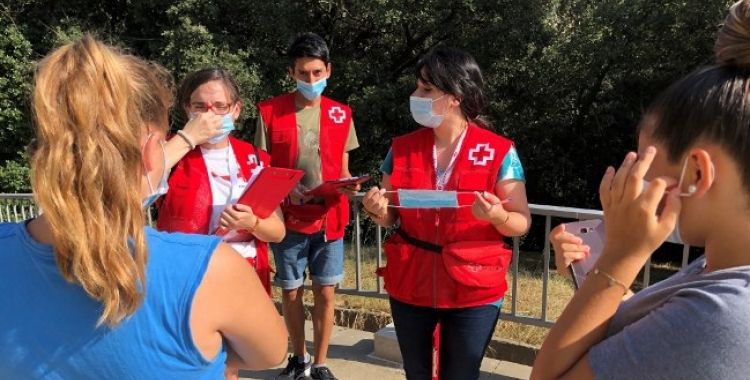 Voluntaris de Creu Roja Sabadell explicant a unes joves com funciona la mascareta   Cedida