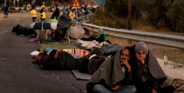 Un grup de persones acampa en una carretera a Lesbos el 2020 | ACN