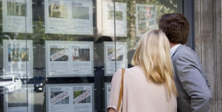 Una parella mirant pisos en una immobiliària