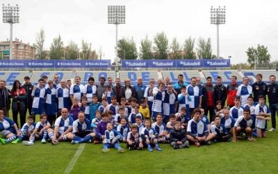 Foto de família a la gespa de la NCA amb els integrants del projecte de futbol inclusiu del CES