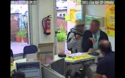 Imatge captada per una càmera de videovigilància en la qual es veu com un home apunta amb una arma un client en una oficina de Correus. ACN