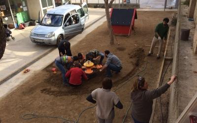 Pares, mares i mestres de l'Escola Nostra Llar treballant en el pati | Cedida