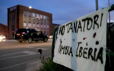 Pancarta contra el tanatori amb la nau que podria acollir-lo de fons.