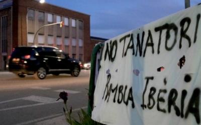 Pancarta contra el tanatori amb la nau que podria acollir-lo de fons | Mireia Prat