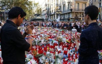 Dos joves aplaudeixen després d'haver fet l'ofrena a les víctimes dels atemptats de Barcelona i Cambrils | ACN