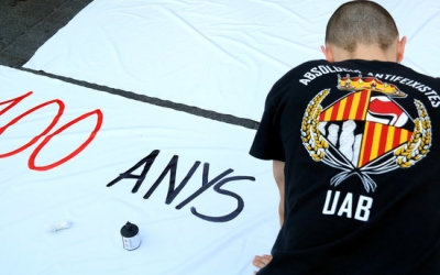 Estudiant escrivint cartell a l'acampada indefinida a la plaça Universitat | ACN