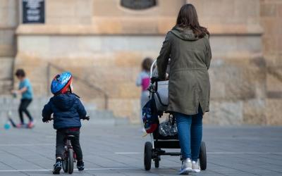 Imatge d'una mare amb els fills passejant a plaça Sant Roc | Roger Benet