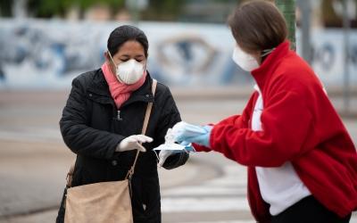 Una voluntària de Creu Roja repartint mascaretes/ Roger Benet
