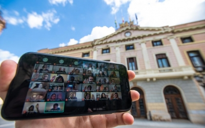 L'exterior de l'Ajuntament, amb la sessió telemàtica en un mòbil/ Roger Benet