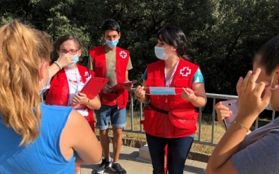 Voluntaris de Creu Roja Sabadell explicant a unes joves com funciona la mascareta | Cedida