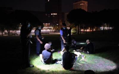Agents de la policia expliquen a un grup de joves que està prohibit beure a la via pública