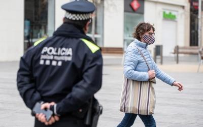 Un policia davant una dona amb mascareta/ Roger Benet