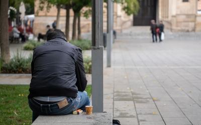 Una persona en un banc de plaça Sant Roc/ Roger Benet