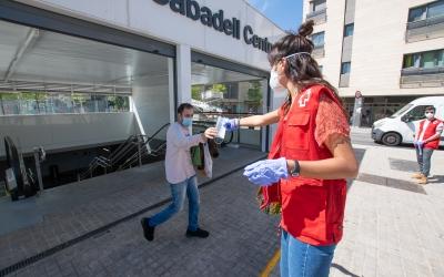 Una voluntària de Creu Roja donant mascaretes a l'entrada de Sabadell Centre | Roger Benet