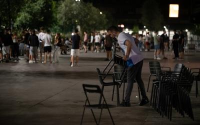 Un cambrer recull una terrassa mentre diverses persones es concentren al Passeig | Roger Benet