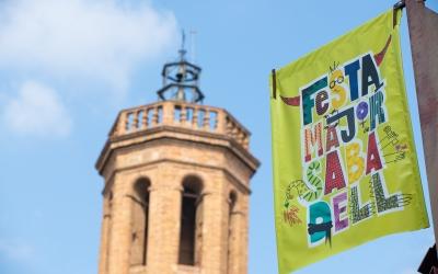 Un cartell de Festa Major, amb el campanar de Sant Fèlix de fons/ Roger Benet