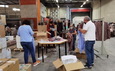 Els voluntaris ordenen i classifiquen les peces de roba de l'outlet   Cedida