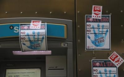 Caixer del Banc Sabadell ple de cartells en contra de l'ERO que ha plantejat l'entitat | ACN